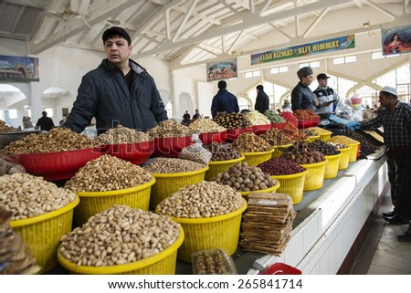 BUKHARA, UZBEKISTAN - MARCH 16, 2015: City grocery market. Man sells nuts and dried fruits. - stock photo