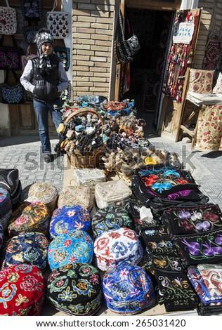 BUKHARA, UZBEKISTAN - MARCH 16, 2015: Gift shop. Giirl sells national headgear - the skullcap. - stock photo