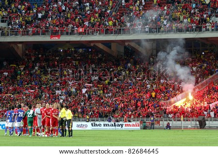 BUKIT JALIL - JULY 16: A flare lights up as Liverpool players wave to supporters after the match against Malaysia at the National Stadium on July 16, 2011, Bukit Jalil, Malaysia. Liverpool won 6-3.