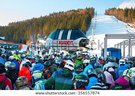 BUKOVEL, UKRAINE - DEC 08, 2015: Crowd in queue for a ski lift in Bukovel. Bukovel is the most popular ski resort in Ukraine, in 2012 was named the fastest-growing world ski resort. - stock photo