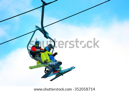 BUKOVEL, UKRAINE - DEC 08, 2015: Skier and snowboarder on a ski lift in Bukovel. Bukovel is the most popular ski resort in Ukraine.