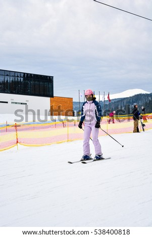 BUKOVEL, UKRAINE - December 17, 2016: Skiers and snowboarders enjoying on slopes of ski resort Bukovel, Ukraine. Bukovel is the most popular ski resort in Ukraine. Ski season and Winter sport.