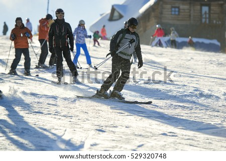 BUKOVEL, UKRAINE, DECEMBER 20, 2015: skiers and snowboarders on a training slope in the morning