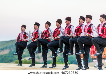 "BUKOVO, BULGARIA - JULY 23, 2016: Male dancers in traditional Bulgarian folklore costumes are smiling while performing a fast dance during Bulgarian outdoor folklore gathering ""Ugar"""