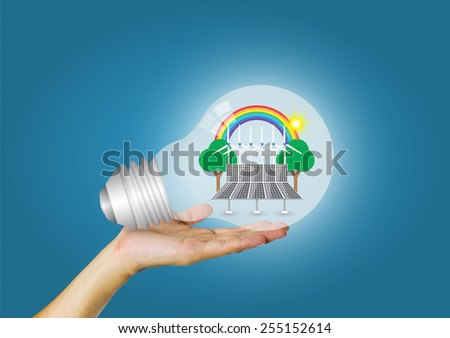 Bulb and alternative energy in hand with blue background. - stock photo