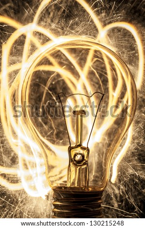 bulb and sparklers on black background - stock photo
