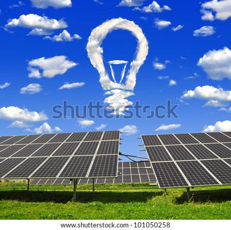 Bulb from clouds above the solar energy panels - stock photo