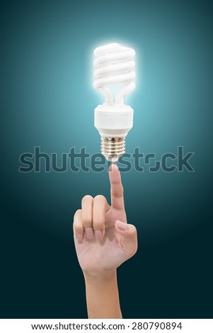 Bulb light on women Fingertip on blue background - stock photo