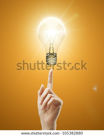 bulb light on women fingertip on orange background - stock photo