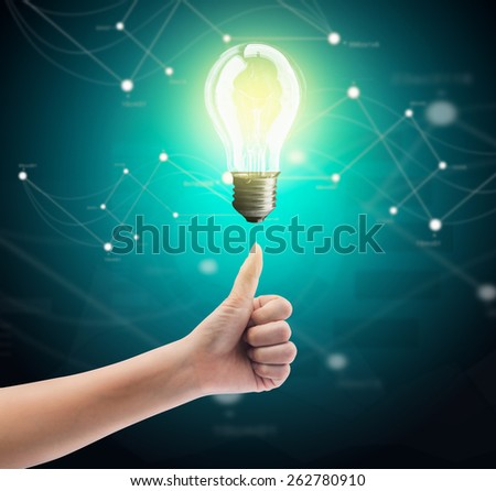 Bulb light on women thumb on green background - stock photo