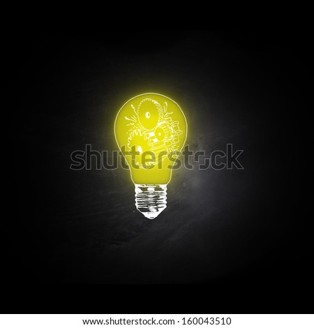 bulb of yellow light on black space