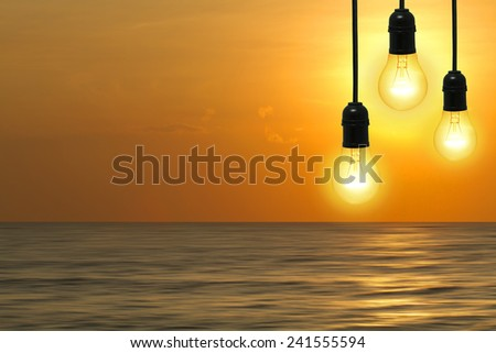 Bulb of yellow light with a background as the sky at sunset in the sea - stock photo