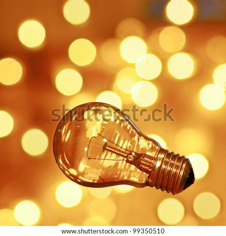 Bulb on gold background with bokeh - stock photo