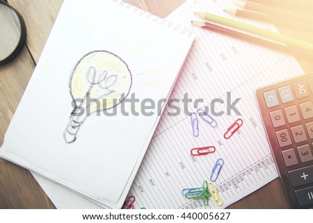bulb on  notebook, calculator and  pencils on working table