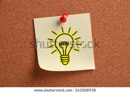 Bulb sign sticky note is pinned on cork. - stock photo