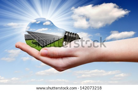 Bulb with of solar panel in hand - stock photo