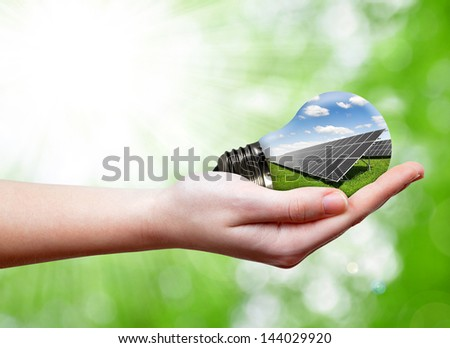 Bulb with of solar panel in hands on green background - stock photo