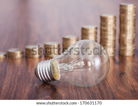 Bulb With Stack Of Coins Placed On Table - stock photo