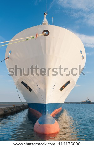 Bulbous bow of dry cargo ship docked in harbor - stock photo