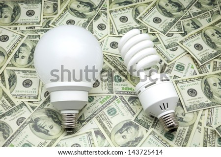 bulbs of low consumption on dollars  - stock photo