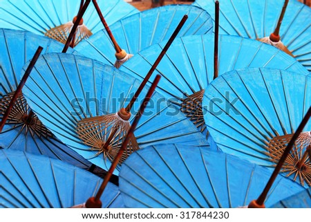 Bule cotton umbrellas at a handicraft festival in Bo Sang, Chiang Mai, Thailand. Shallow depth of field with the nearest umbrella in focus. - stock photo