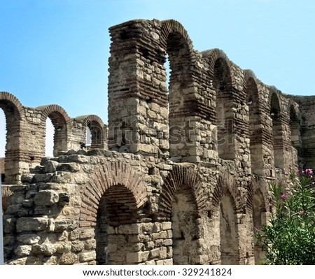 Bulgaria, the ruins of an ancient temple, a series of majestic arches, next to the dead stones green flowering bush, sunny summer day.