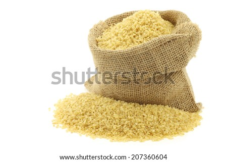 bulgur (couscous) in a burlap bag with an aluminum scoop on a white background - stock photo