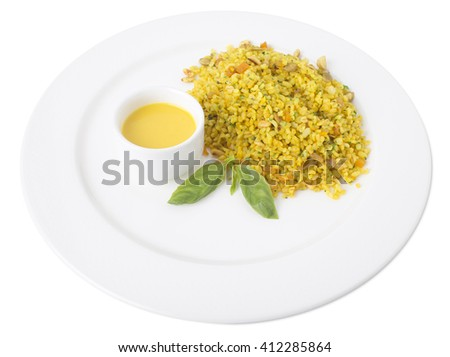 Bulgur porridge with raisins and pumpkin seeds. Served with delicious paprika sauce. Isolated on a white background.