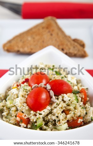 Bulgur salad with tomatoes, cucumber and cheese - stock photo