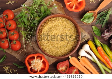 Bulgur (wheat dried fragmented) in a clay bowl on a brown wooden background. Near vegetables such as red peppers; carrot; onions, tomatoes. Vegetarian concept. Healthy eating - stock photo