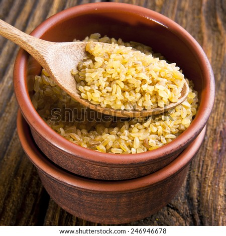 Bulgur wheat in bowl with spoon on brown background - stock photo