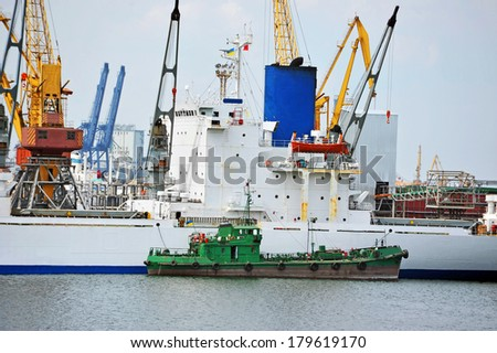 Bulk cargo and bunker ship under port crane - stock photo