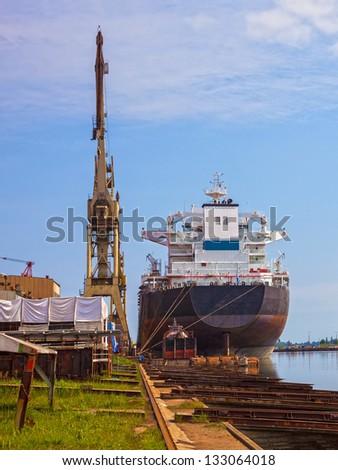 Bulk cargo ship under port crane. - stock photo