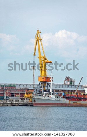 Bulk cargo ship under port crane bridge, Odessa, Ukraine - stock photo
