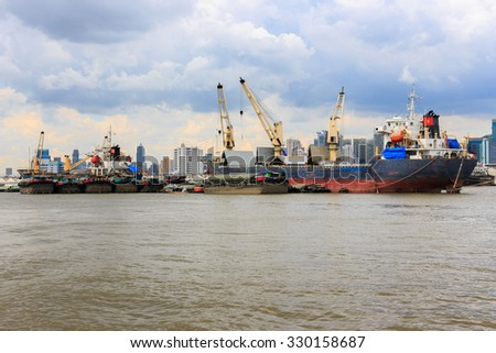 Bulk cargo ship unloading their cargo in the Chao Phraya River, Bangkok Port, Thailand