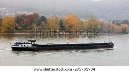 Bulk-carrier barge on waterway river Rhine with autumn fall colored landscape on shore, North Rhine-Westphalia, Germany, Europe - stock photo