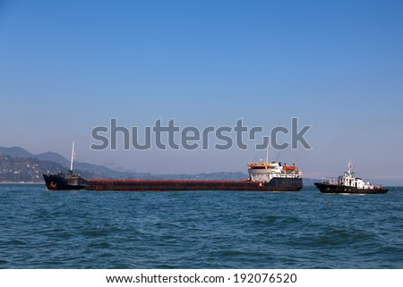 Bulk-carrier ship and tugboat moving in the sea  - stock photo