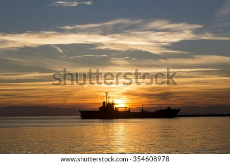 Bulk-carrier ship at sunset in the sea - stock photo