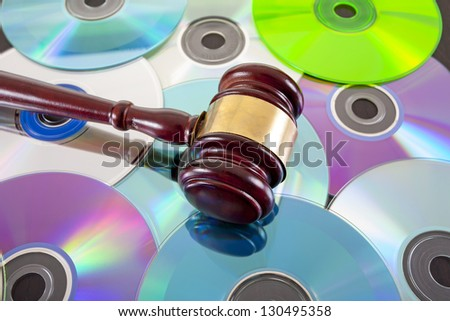 bulk writable colorful compact discs background with gavel on top - stock photo