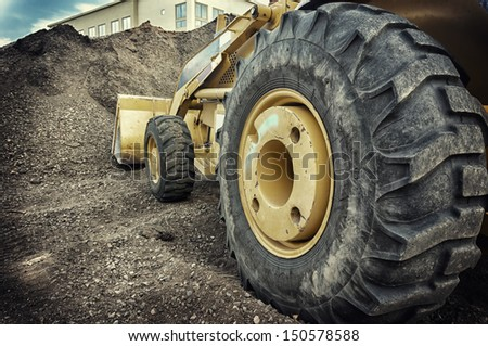 Bull dozer heavy duty construction site focus on large tire. - stock photo