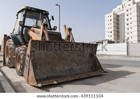Bulldozer at a construction site near the new building - stock photo