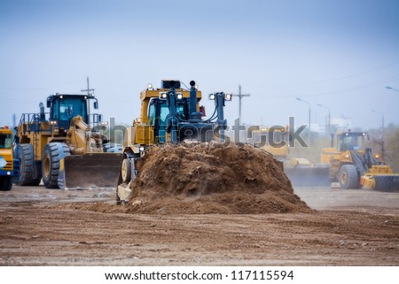 Bulldozer at work with mining machinery on background - stock photo
