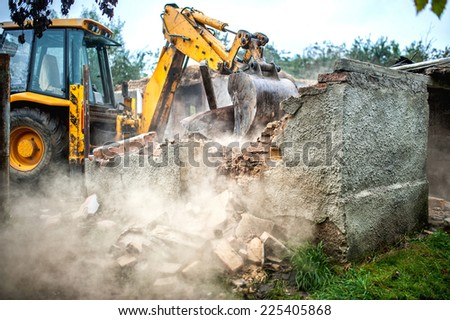 bulldozer demolishing concrete brick walls of small building - stock photo