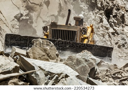 Bulldozer doing mountain road construction in Himalayas. Himachal Pradesh, India