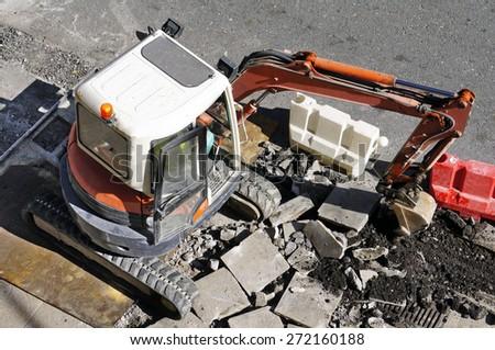 bulldozer excavator machine construction industry picks up debris on city street - stock photo