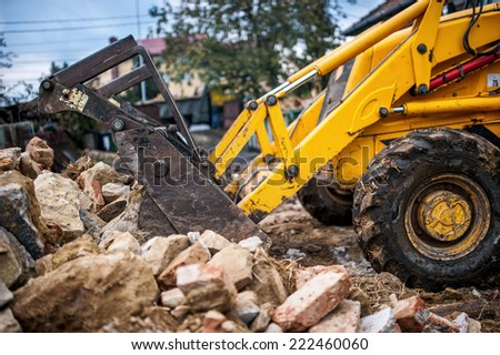 bulldozer loading demolition debris and concrete waste for recycling at construction site - stock photo