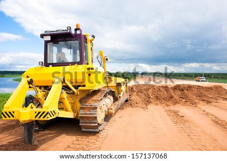 Bulldozer machine during construction road works - stock photo