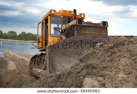 Bulldozer on the banks of the river moves the sand
