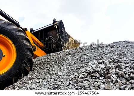 Bulldozer sitting on job site where it is used for clearing gravel for the foundation of a new building. - stock photo