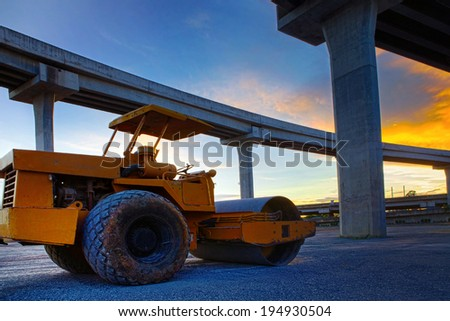 bulldozer tank road construction machine against dusky sky and infra construction of express way - stock photo